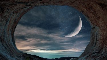 Cave opening onto a view of an exoplanet's moon